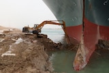 A backhoe is trying to dig out a giant ship that has run aground, the ship is approx 5x as big as the backhoe