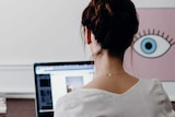 A woman sits at a table typing on a laptop in front of a white wall. An artwork next to her of an eyeball appears to look at her