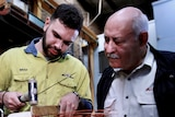 A young man wearing yellow high vis works on some copper wiring while an older man with a moustache watches next to him