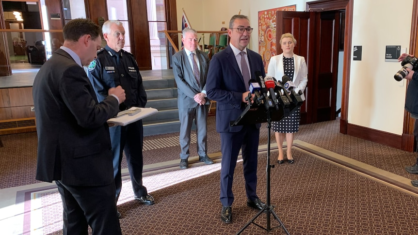 A man in a suit speaks while other people stand behind him