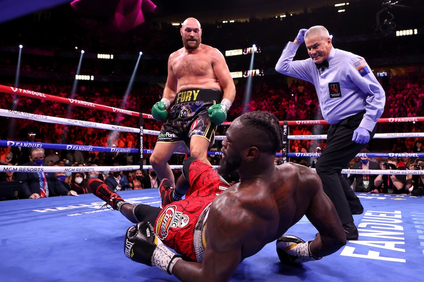 Tyson Fury looks down at Deontay Wilder who has fallen to his back. The referee watches on