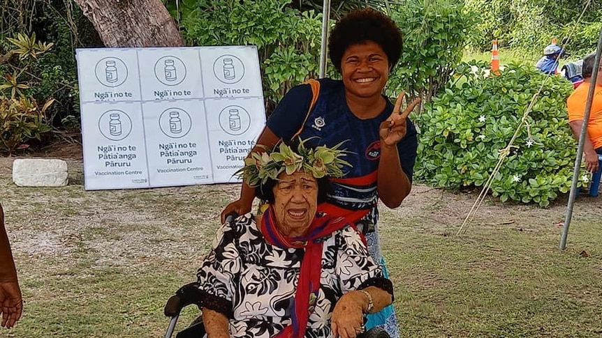 A woman smiles and holds up peace sign while standing behind older woman in wheelchair outside but under cover.