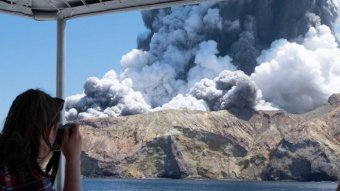 A woman on a boat takes a photo of the volcano on White Island just moments after it erupted.