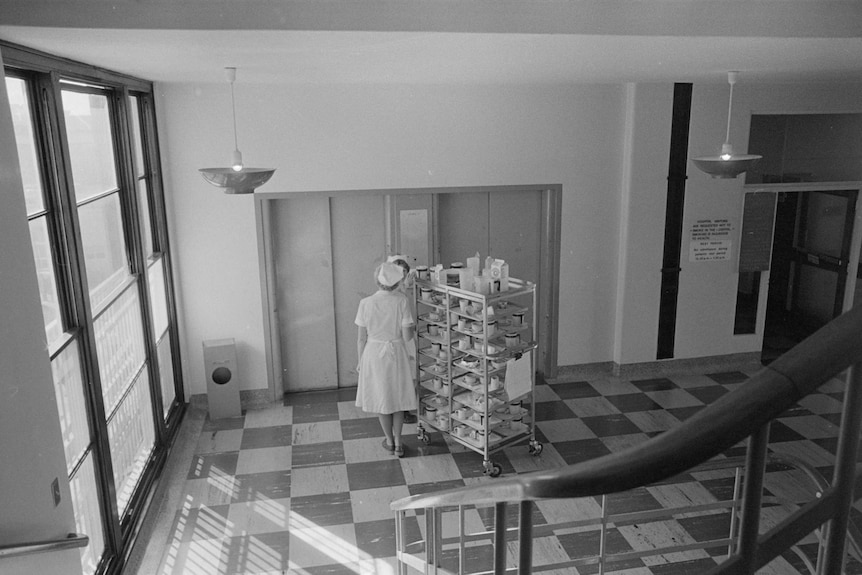 Nurses wheel a trolley filled with crockery into a lift at a hospital.