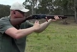 A man aims an adler shotgun