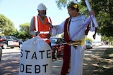 """A man dressed as an emperor in robes and another in a hard hat holding a bag marked """"state debt"""" stand on a street."""