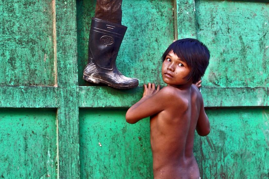 A boy scales a bin at a Cambodian rubbish dump