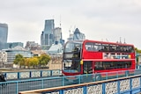 """A London bus drives across the bridge with a sign saying """"powered by coffee beans""""."""