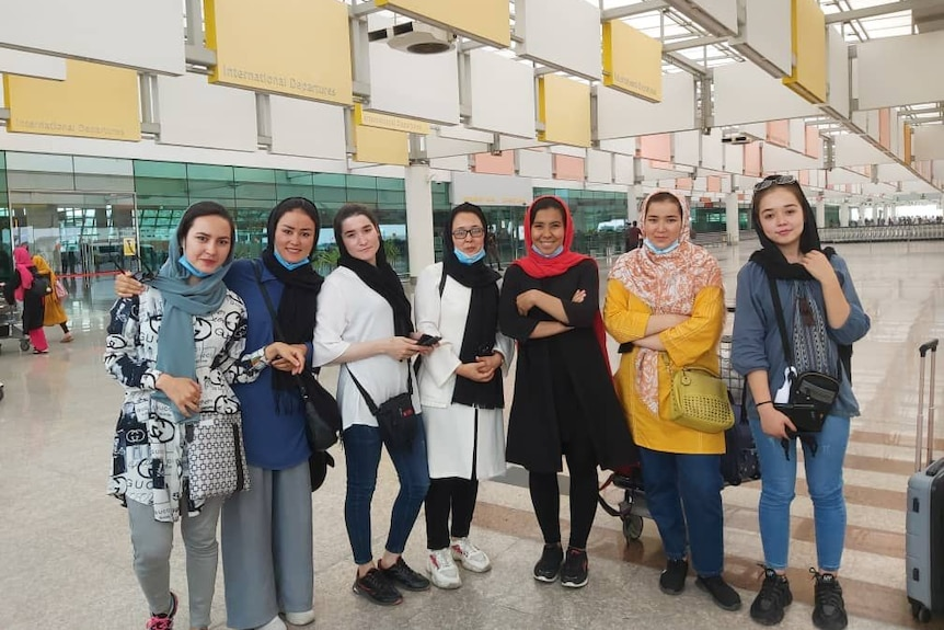 Seven women standing side by side at the airport