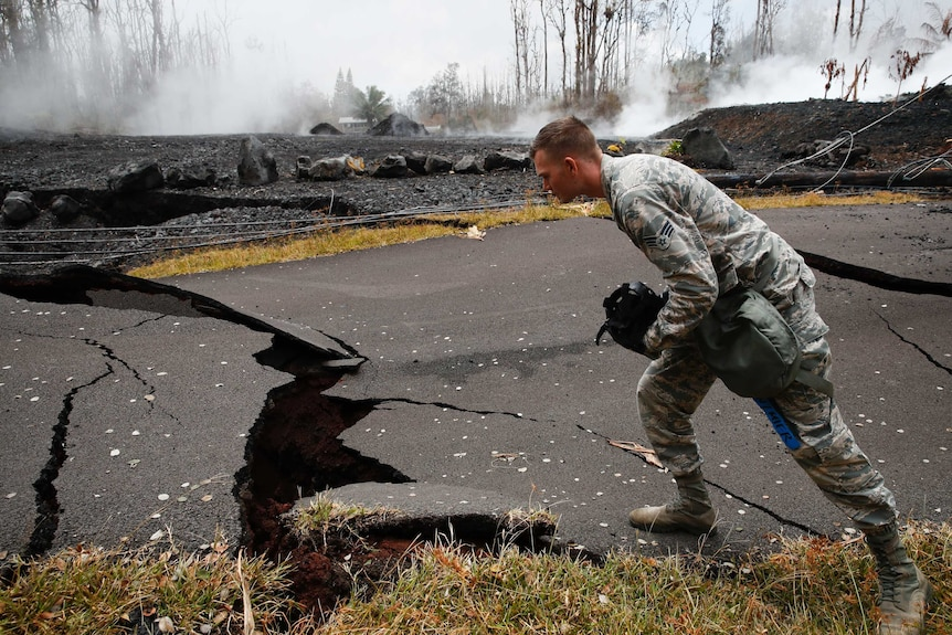 A U.S. Air National Guardsman looks at cracks as toxic gases rise from a crack in the road