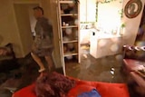 A main wades through flood waters in his living room.