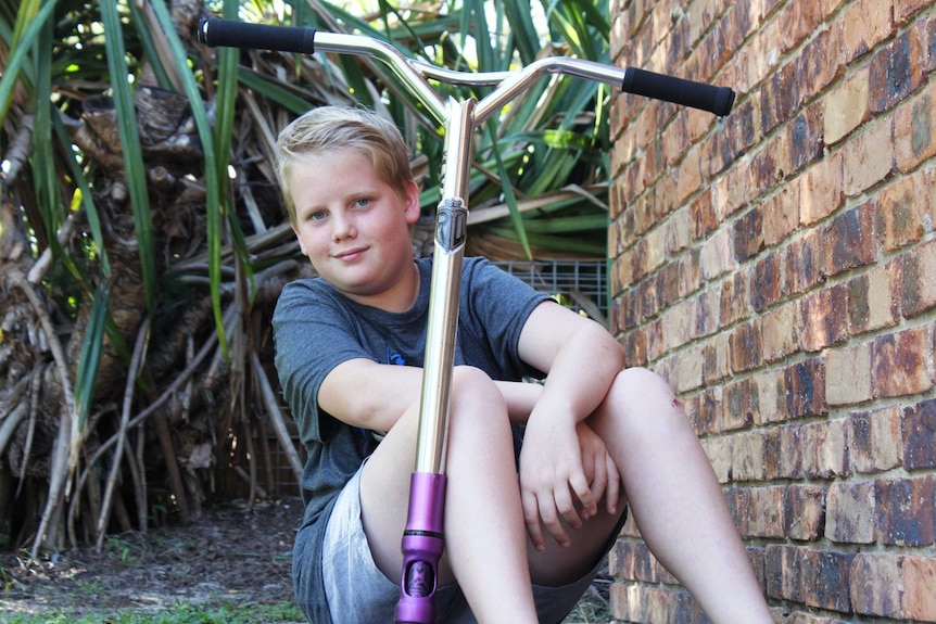 13yo Oliver, who has Tourette syndrome, sits smiling on his scooter