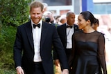 Prince Harry laughs and looks down as he walks next to Meghan holding her hand. She looks to him, and they are both in black tie
