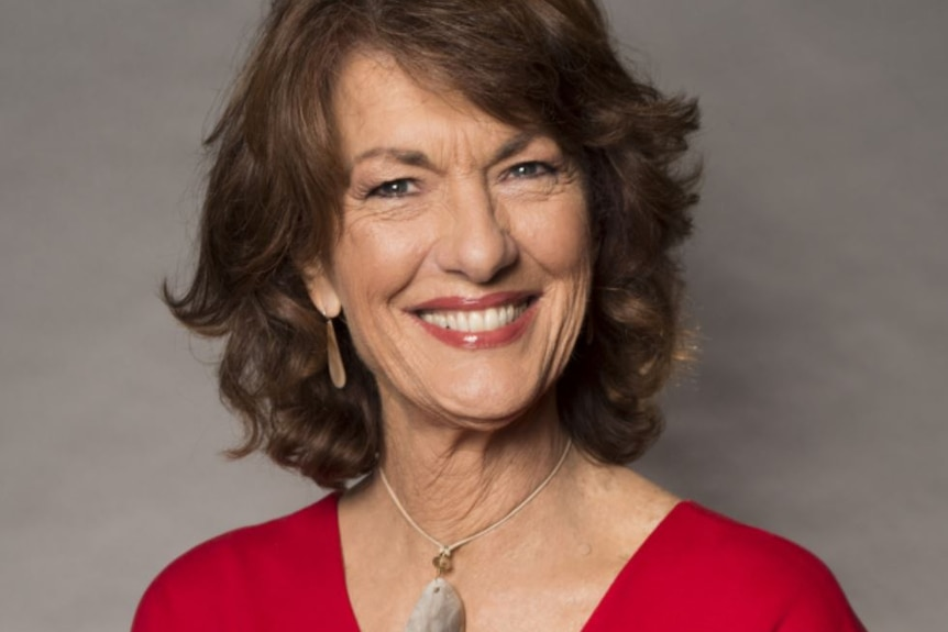 Geraldine Doogue, with wavy brown hair and wide smile, wears a red top with a small silver necklace.