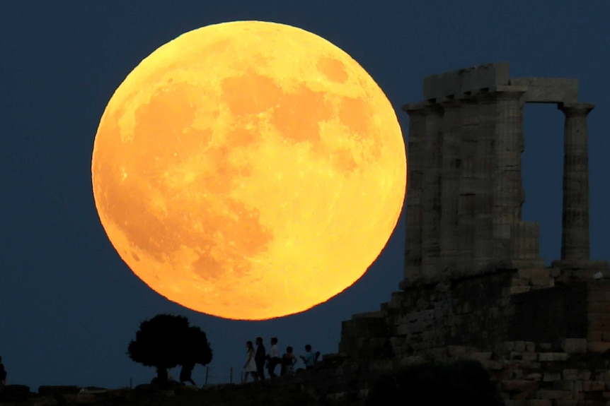 People watch a full moon rising behind the Temple of Poseidon.