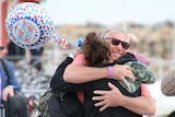 """A man and daughter embrace and smile on a wharf while she holds a colourful balloon that says """"welcome home""""."""