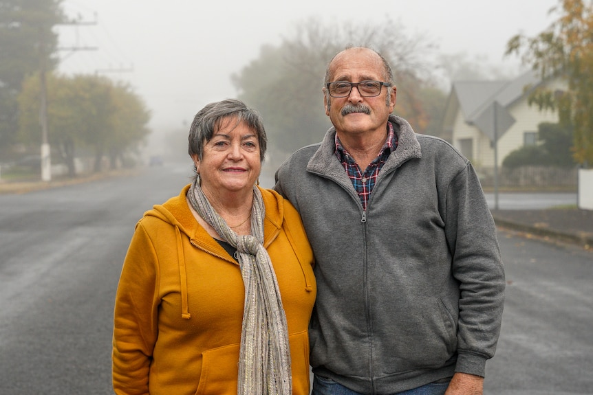 An older man and woman stand for a photo in a foggy street with their arms around each other.