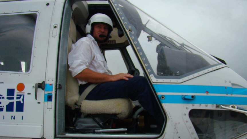 A man sitting at the controls of a helicopter