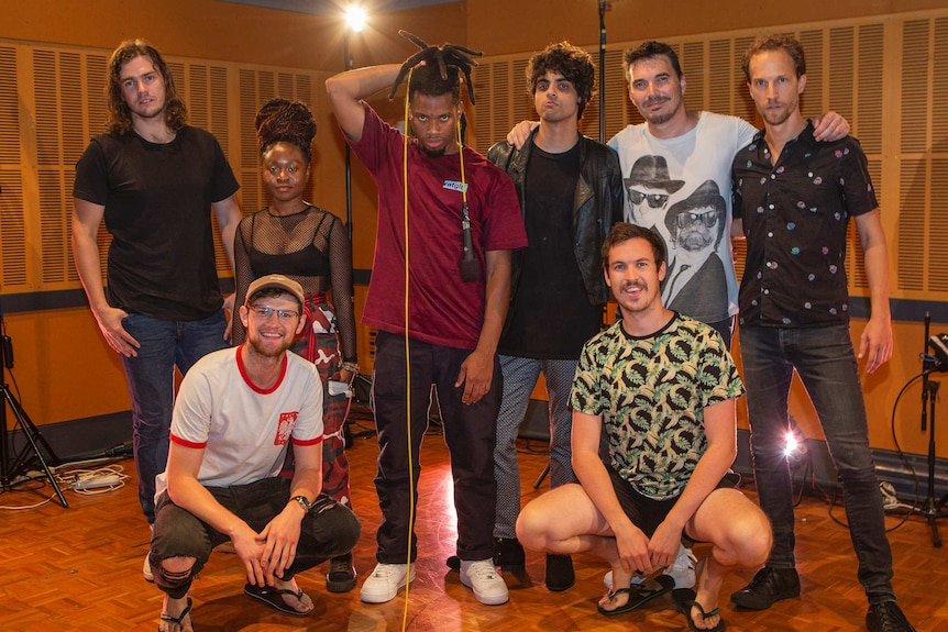 Group shot of band in studio with Curry holding microphone cord over head and Harvey and Stapleton in front row.