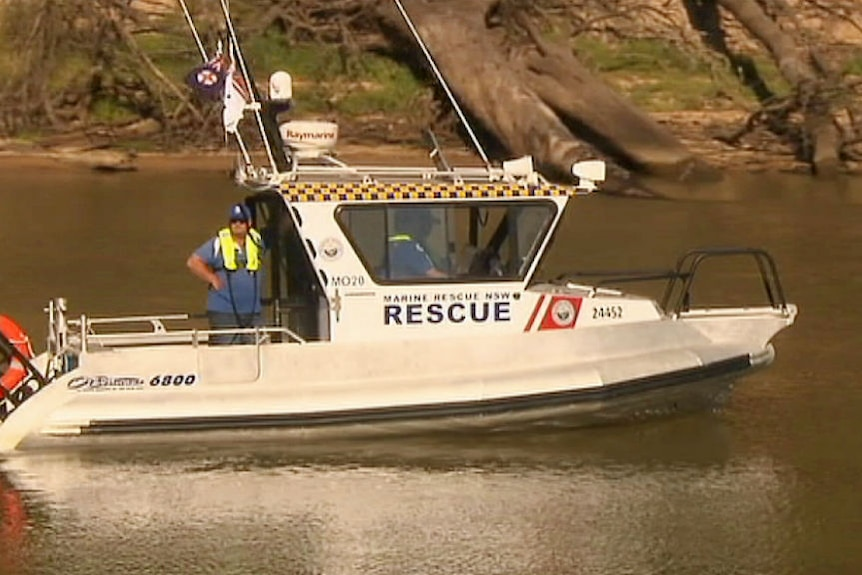 A police boat on a river with officers looking into the water