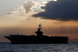 The silhouette of the USS Theodore Roosevelt aircraft carrier against a dramatic sunset, near Manila.