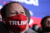 A woman with a red mask bearing the word Trump looks beyond the camera