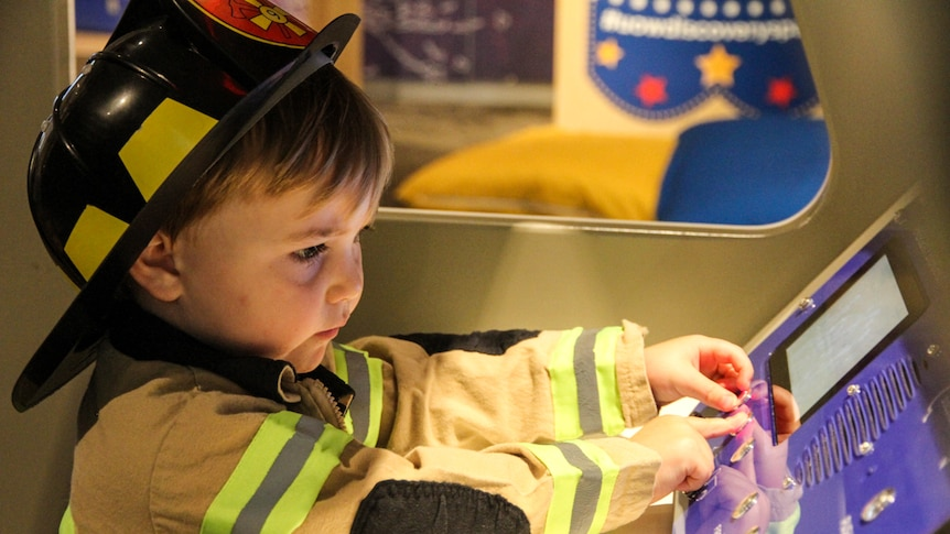 A little boy, dressed up as a fireman, plays in an interactive museum