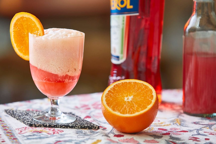 Aperol float in a glass next to an orange to depict a collection of low-alcohol cocktail recipes.