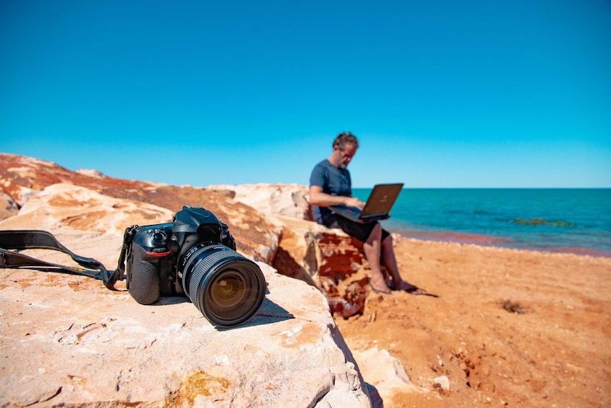 Camera on rock and man behind on laptop, with ocean in background.