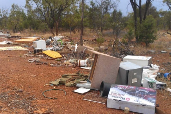 Furniture, whitegoods, electricals and other miscellaneous waste has been dumped on the side of a road girt by red dirt.