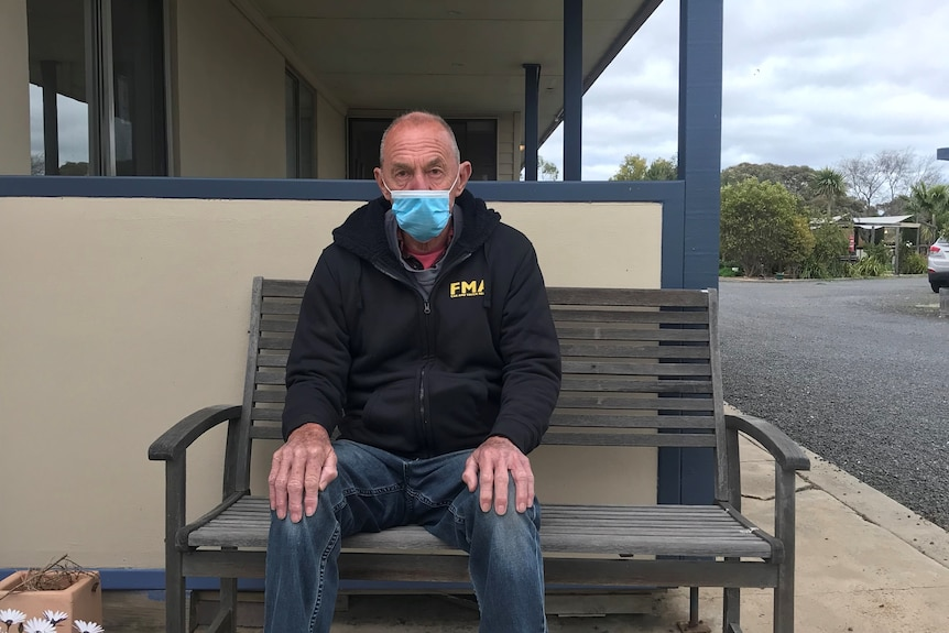 An old man wearing a mask sits on a bench out the front of a motel.
