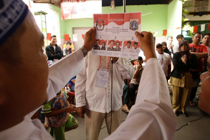 A side profile of a man holding the ballot paper for the election, people in the background look at him.