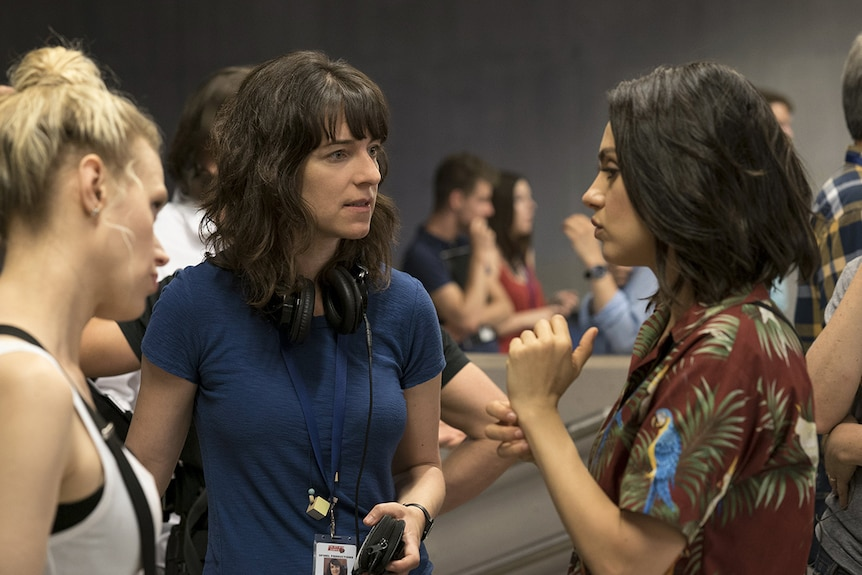 Colour photograph of director Susanna Fogel speaking to actors Mila Kunis and Kate McKinnon on set.
