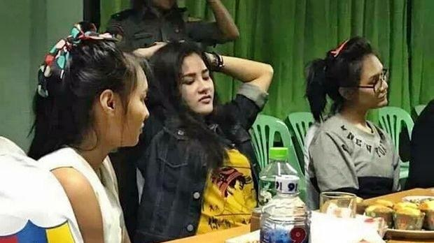 """Preeyanuch """"Preaw"""" Nonwangchai (centre) and two alleged accomplices sit at a table after turning themselves in."""