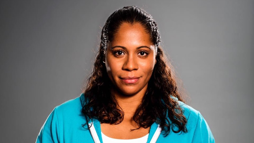Shareena Clanton smiles, wearing a blue tracksuit standing against a grey backdrop.