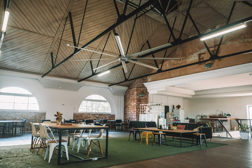 Large room with natural light filled with groups of desk and chairs