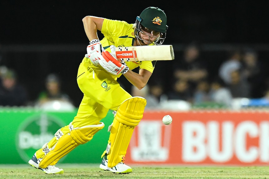An Australia female batter plays a shot to the off side against India.