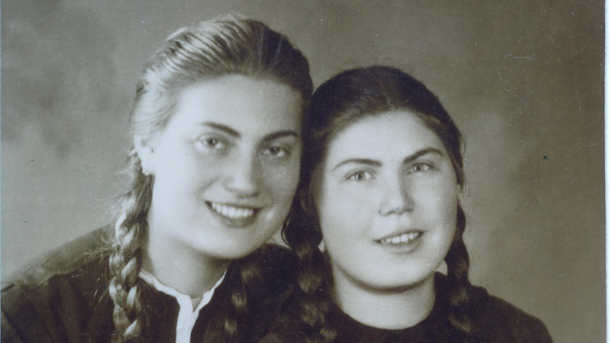 A black and white portrait of two young women smiling at the camera with long plaited hair.