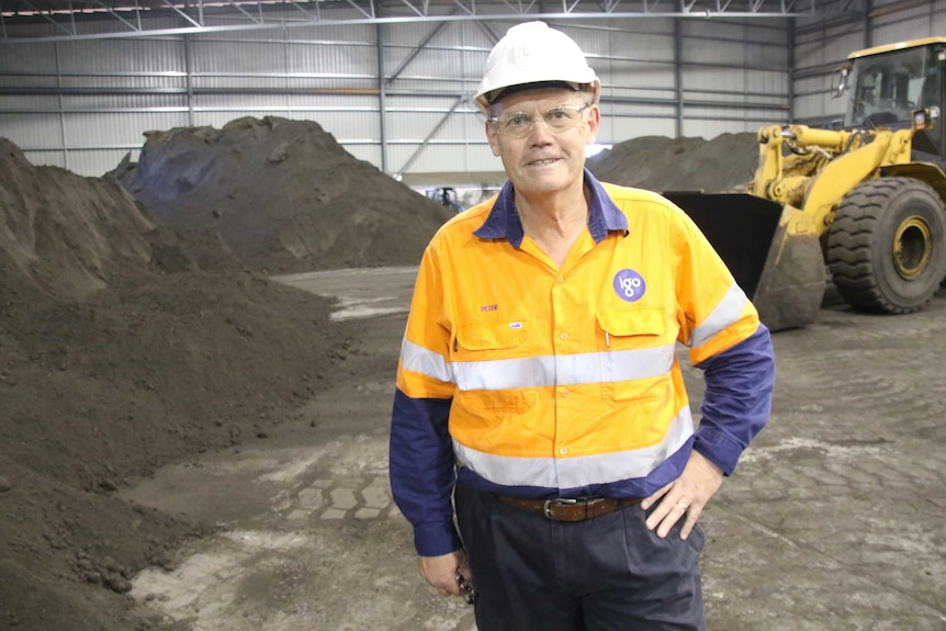 A mine worker standing in front of nickel concentrate stockpiles.