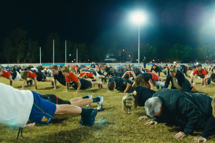 Scoresof players, coaches and support staff at the Morningside AFL club in Brisbane doing push-ups on the field.