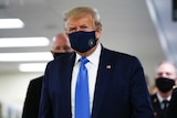 President Donald Trump wears a black face mask as he walks down a hallway.