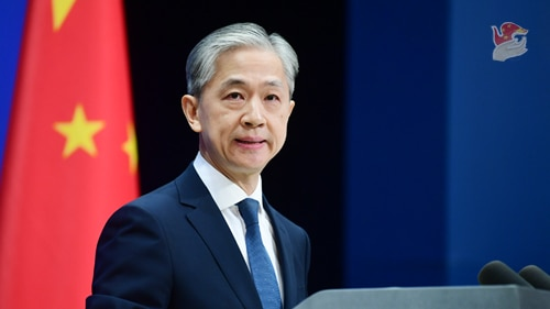 A Chinese man with silver hair speaks at a podium with a ed Chinese flag in the background with yellow stars.