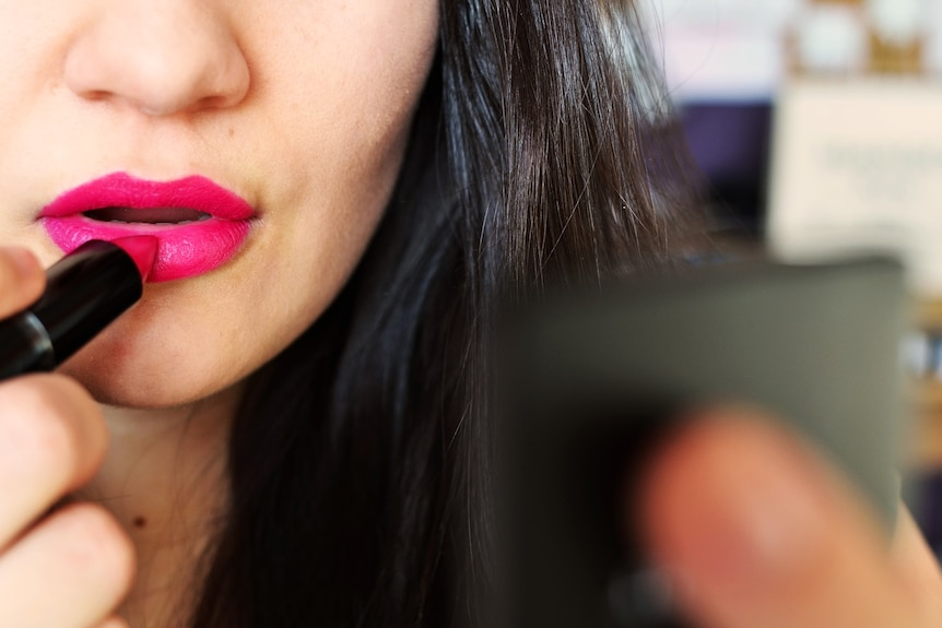 A woman puts on lipstick in a close-up image