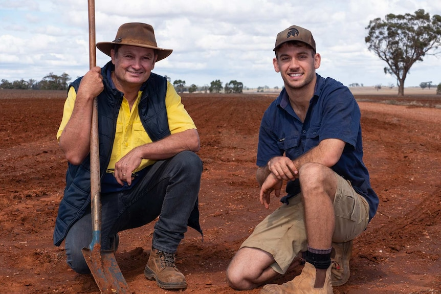 Two men crouch side by side in a paddock with one holding a shovel