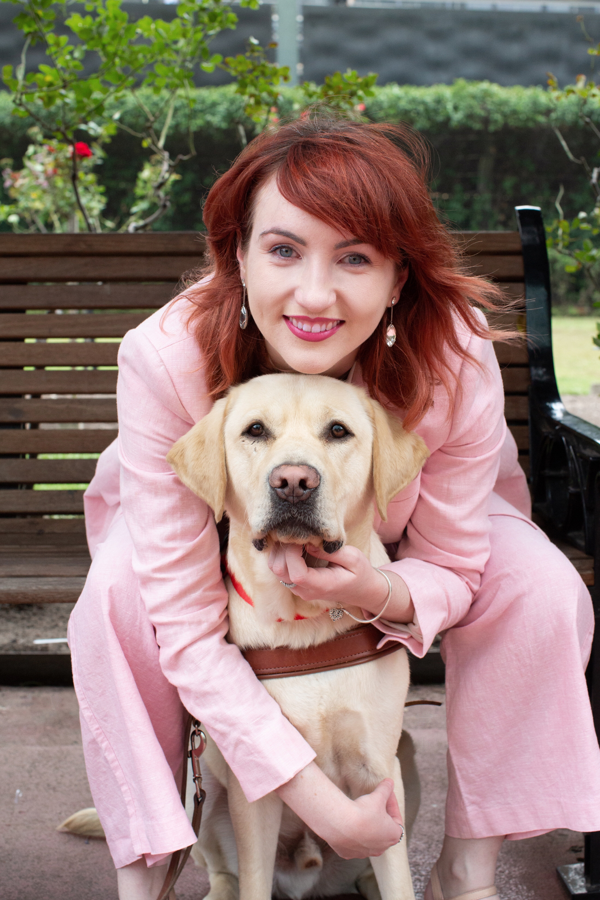 Ingrid wears a pink suit and sits on a bench. She leans to hug her dog Banner who is seated in front of her, facing the camera.