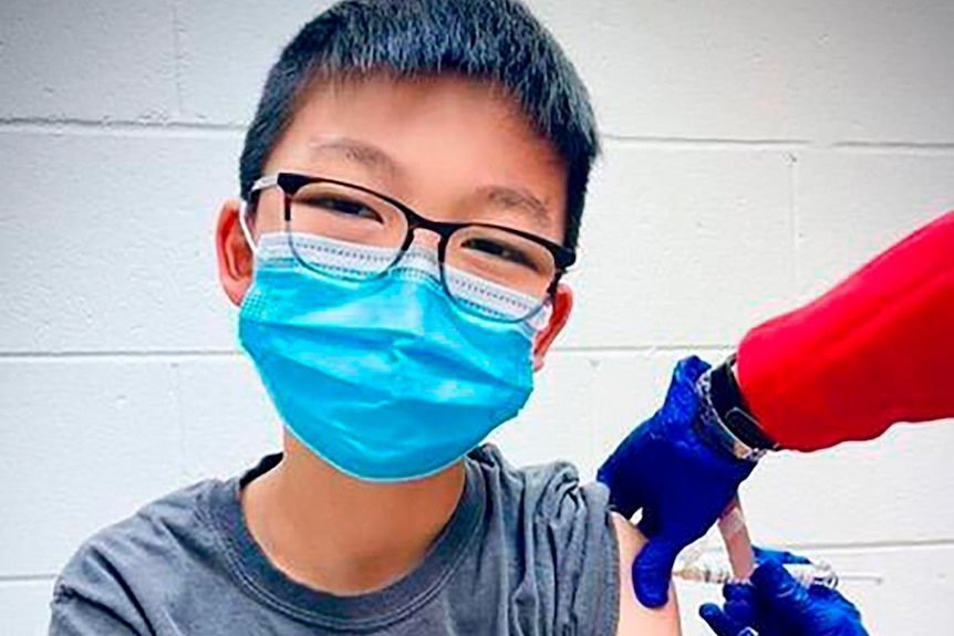 A young boy wearing glasses and a mask looks at the camera as he is vaccinated