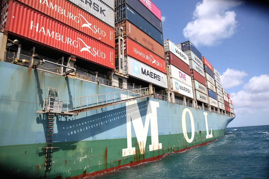 A container ship loaded up with different coloured containers.