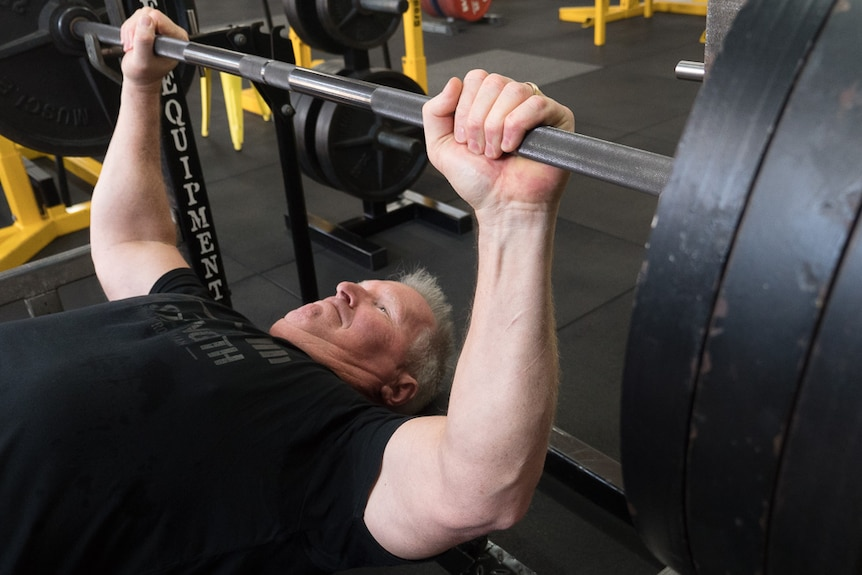 An older man with grey hair bench pressing weights in a gym.