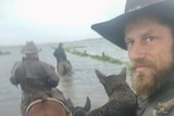 A bearded man in a hat atop a horse in floodwaters looks at the camera. Two other men on horses are ahead.