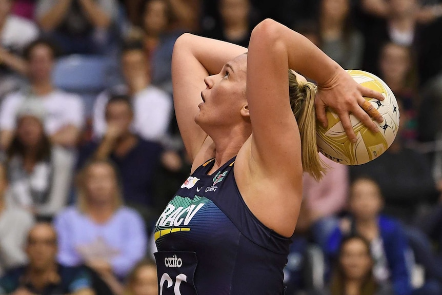 A female netball player holds the ball behind her head as she prepares to shoot for goal.